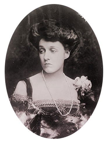Mathilde with dark hair in a bouffant updo, wearing a black beaded evening gown with a white rose corsage at the shoulder.