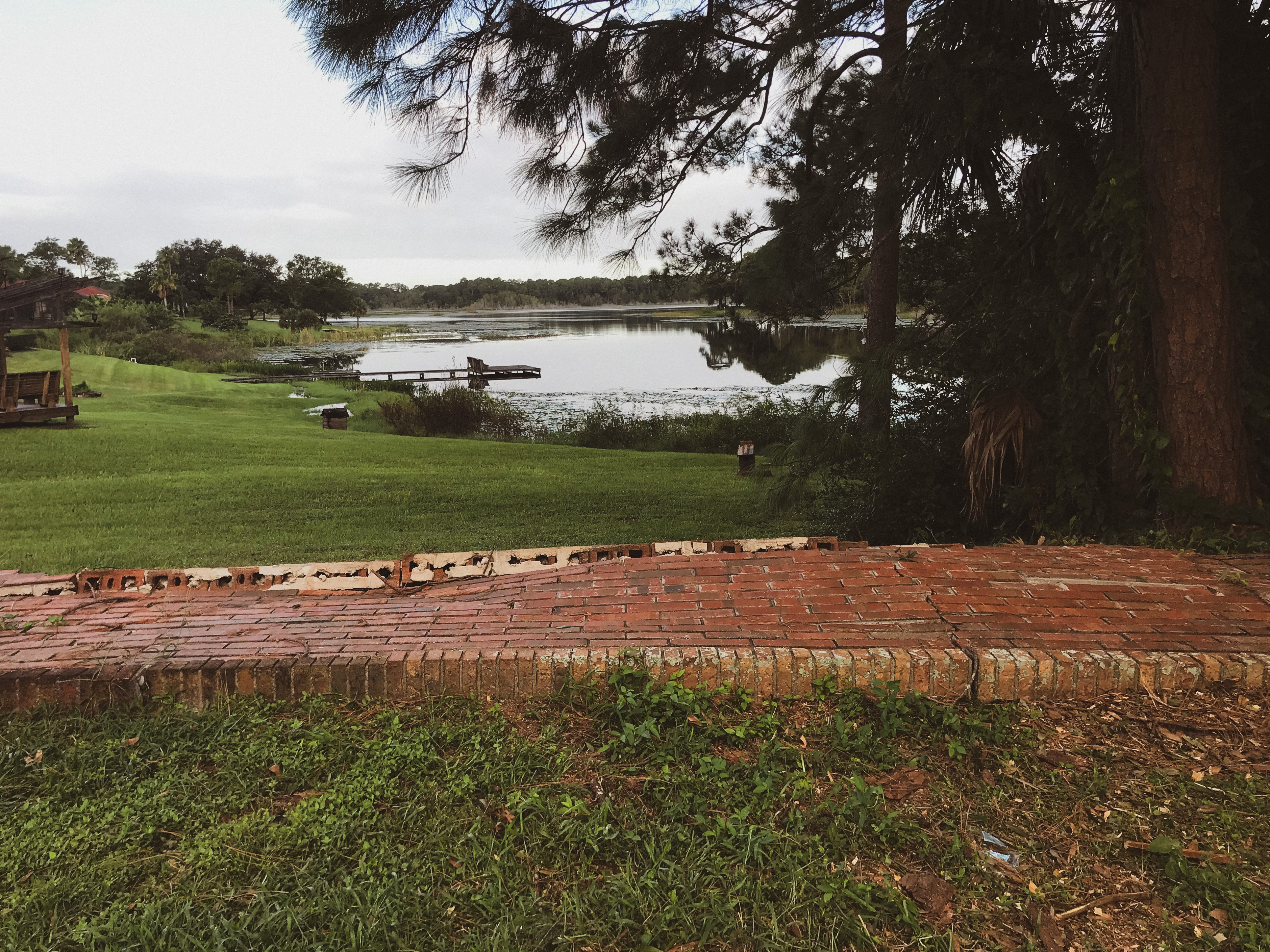 A brick wall knocked over in the storm laying flat, now like a brick pathway might look. Beyond, a dock and a scenic lake.