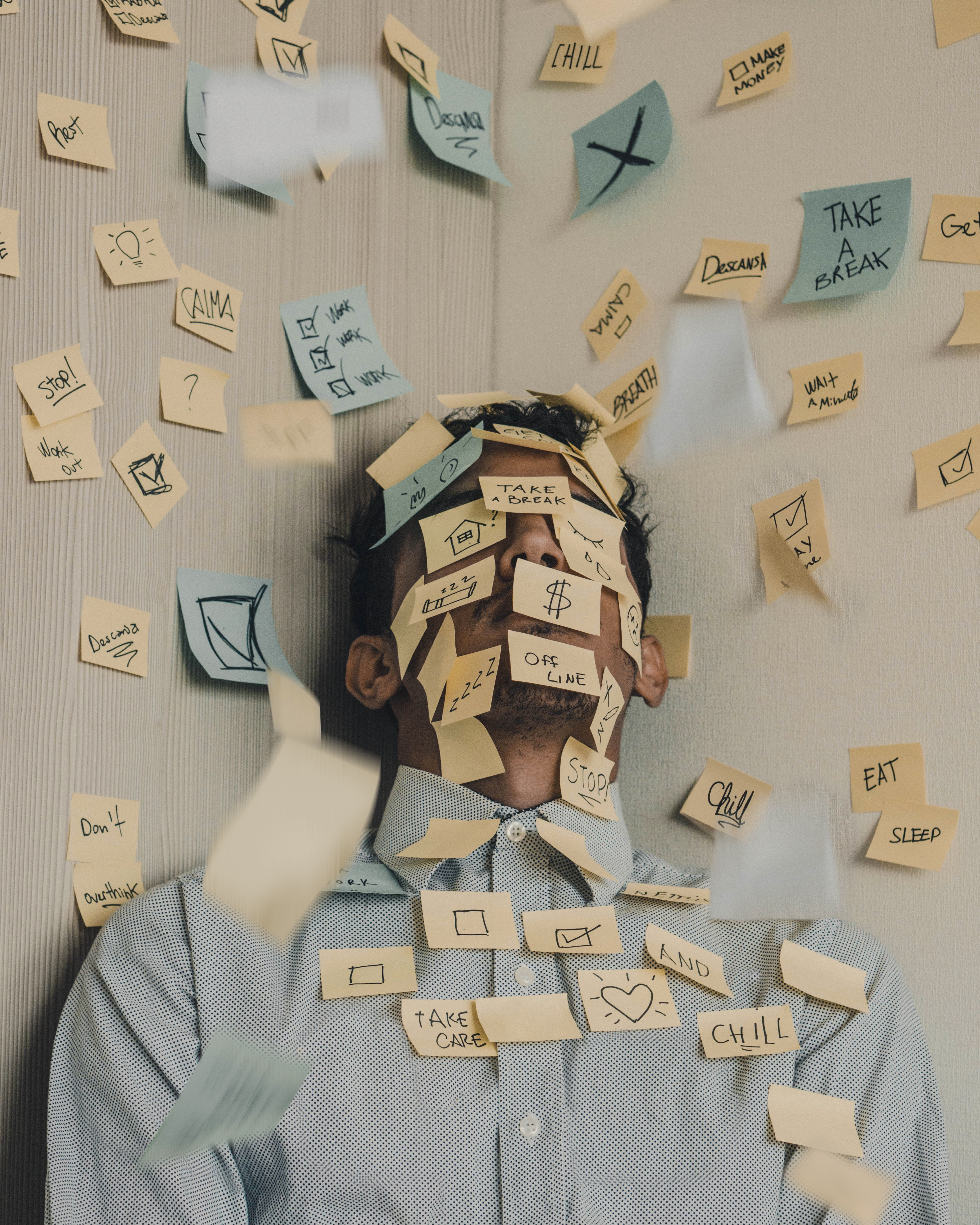 A person stands against a wall with to-do items written on sticky notes on him and the wall. #overwork #productivity