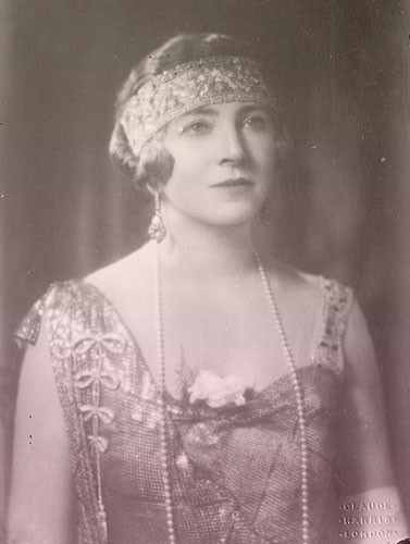 Violet, Duchess of Westminster wears a thick diamond-encrusted bandeau across her forehead and a sleeveless flapper dress.