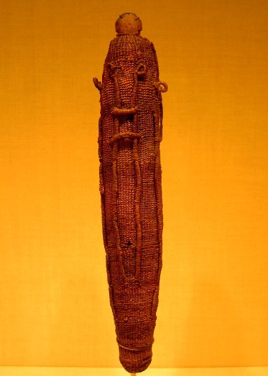 A sacred god figure wrapping for the war god 'Oro, made of woven dried coconut fibre (sennit), which would have protected a Polynesian god effigy (to'o), made of wood. The mana of the god was symbolised by feathers, usually red in colour, which were attached to the surface of the woven covering. Figure held at the Metropolitan Museum of Art in New York.