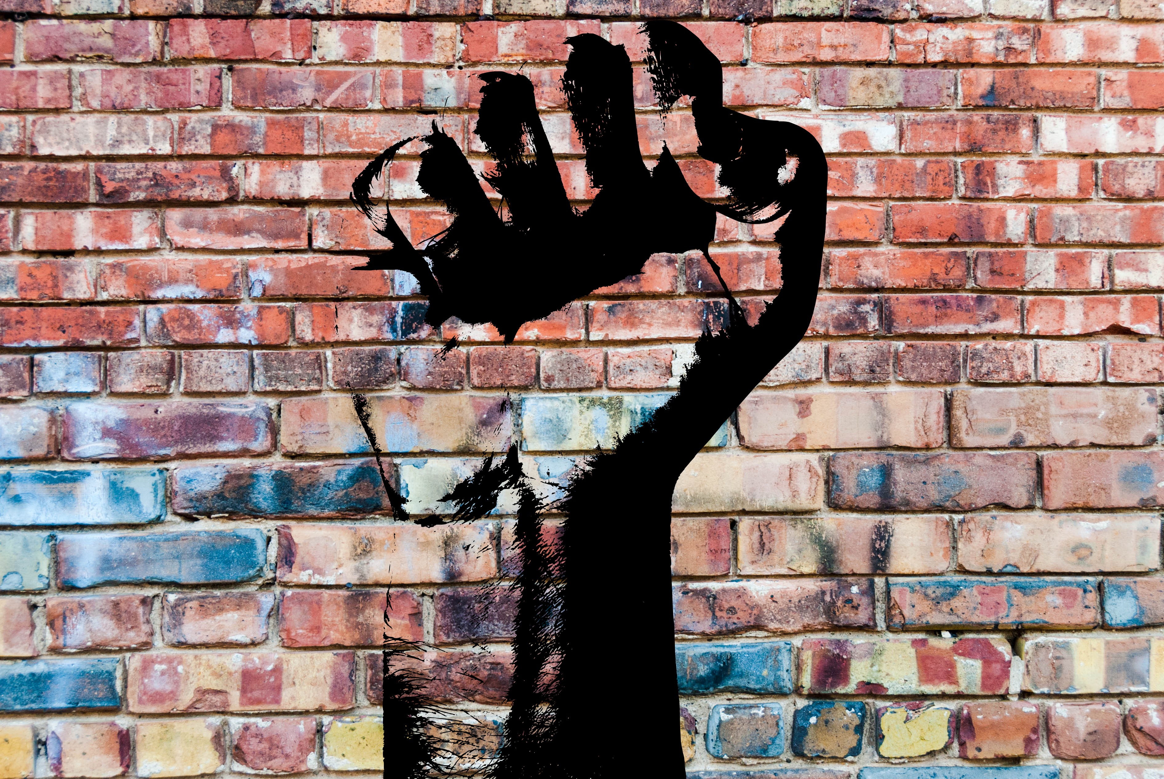 A painted activism power fist in black ink on a multicolored brick wall