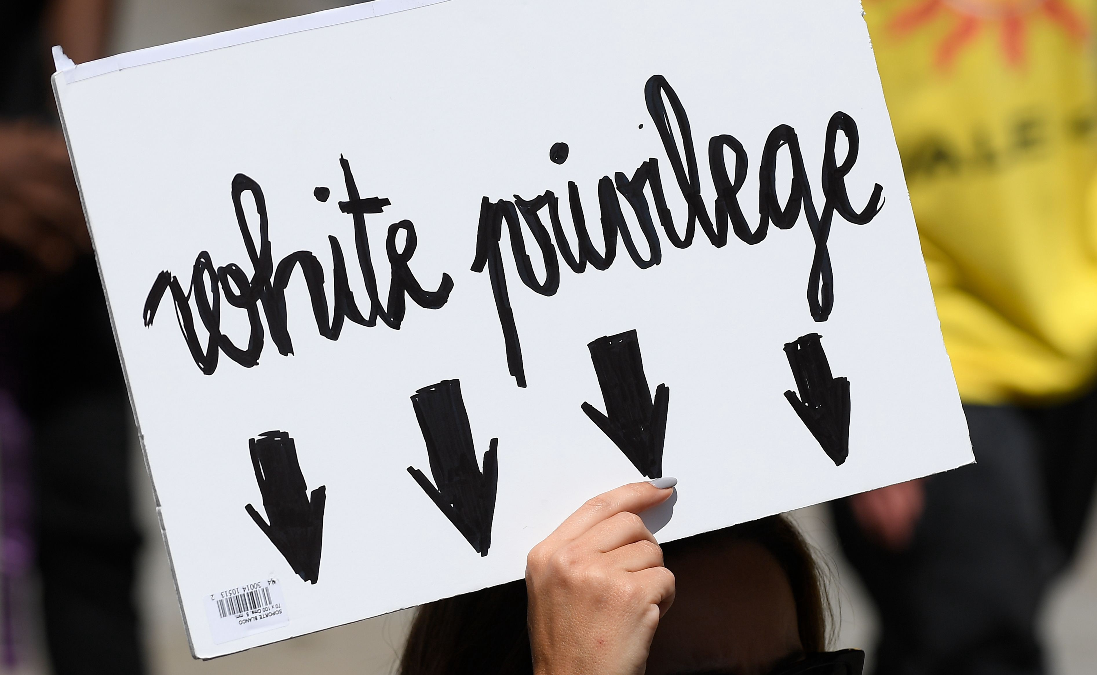 """A woman holding up a sign reading """"White privilege"""" with arrows pointing downward."""