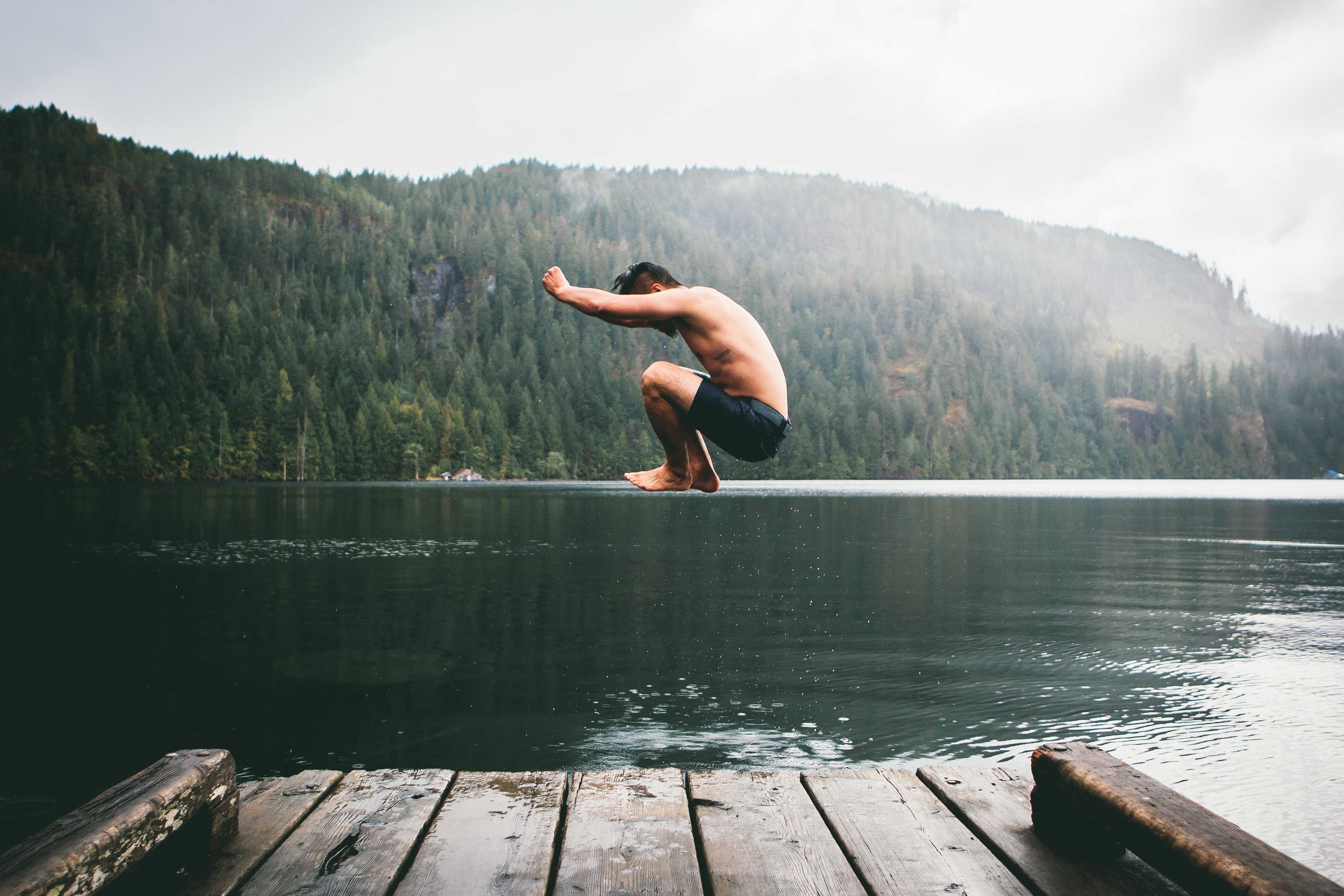 A man jumps into a lake surrounded by a forest