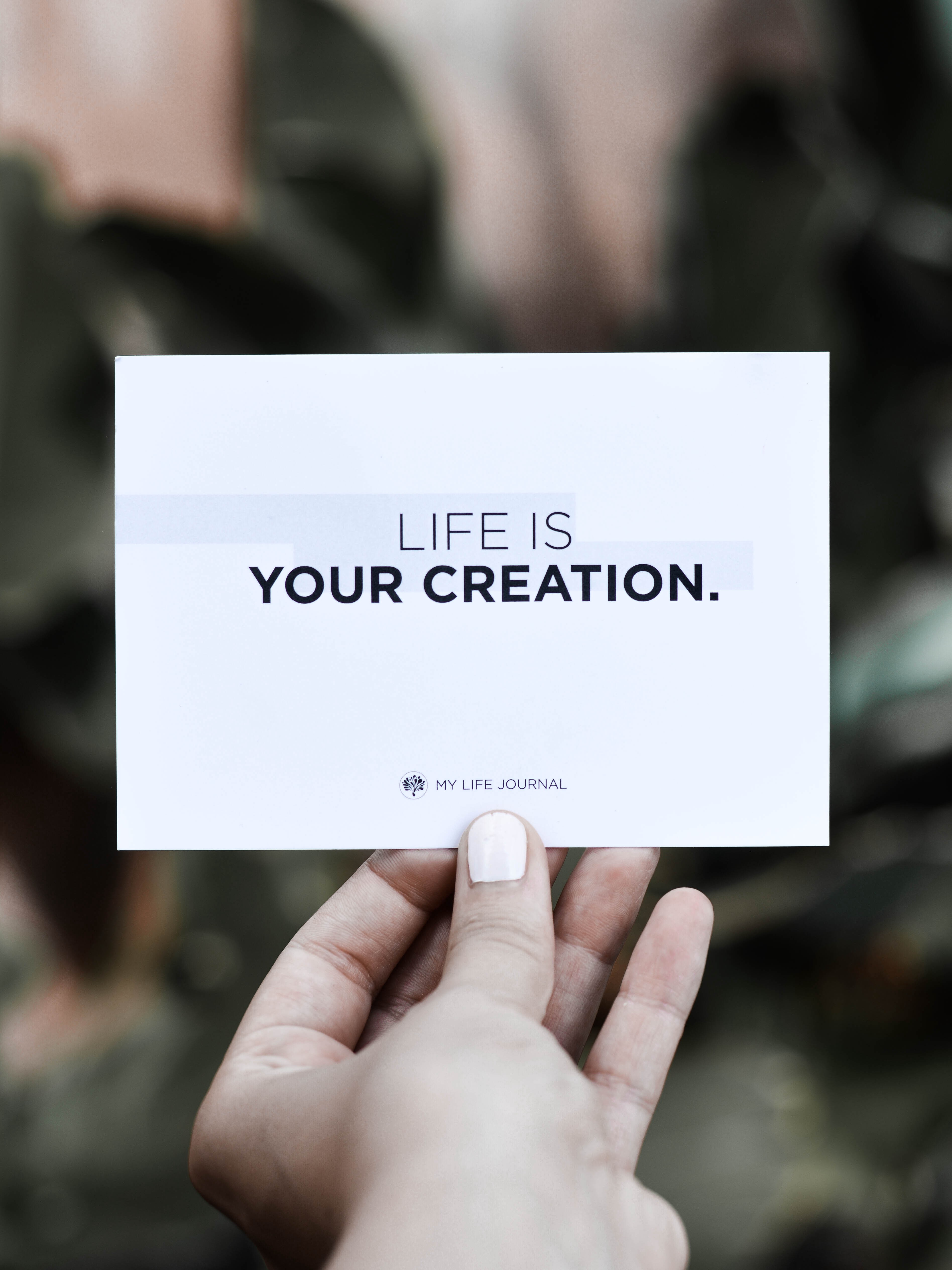"""A picture of a woman's hand holding a white card that reads: """"Life is your creation."""""""