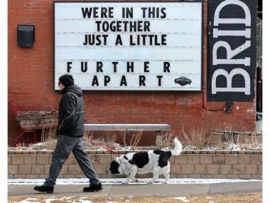 """A man and dog walk past a sign that reads, """"We're in this together. Just a little further apart."""""""