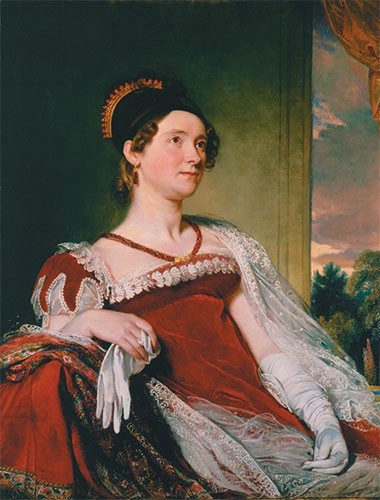 Louisa in a red velvet empire-waist dress with a black cap over her brown curly hair.