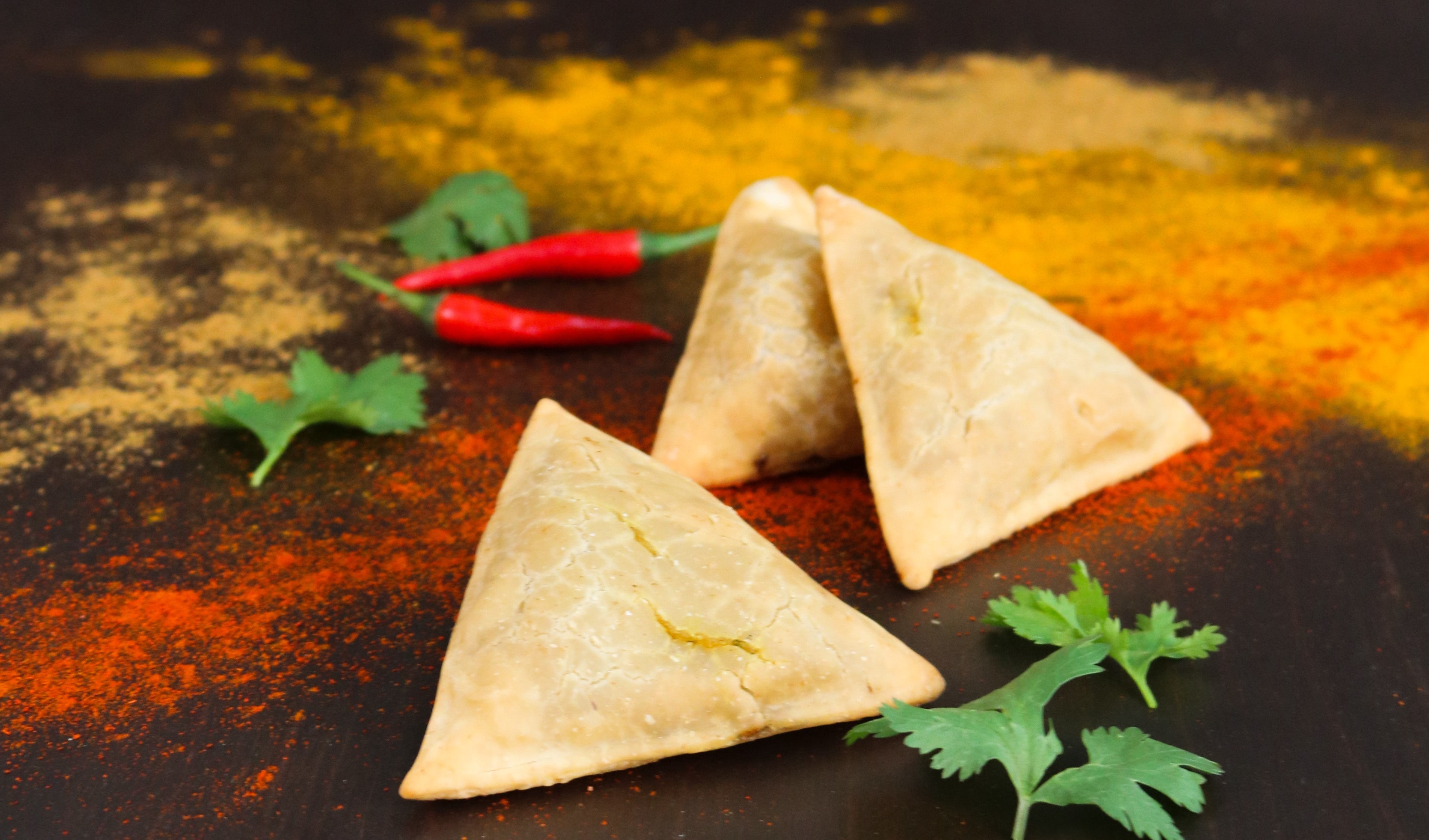 Samosas lie on a worktop next to a few sprigs of coriander and chillies.