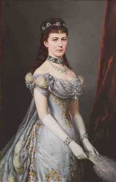 An unsmiling Empress Elisabeth wearing a gorgeous silver low-necked dress with tiny puff sleeves and a long train.