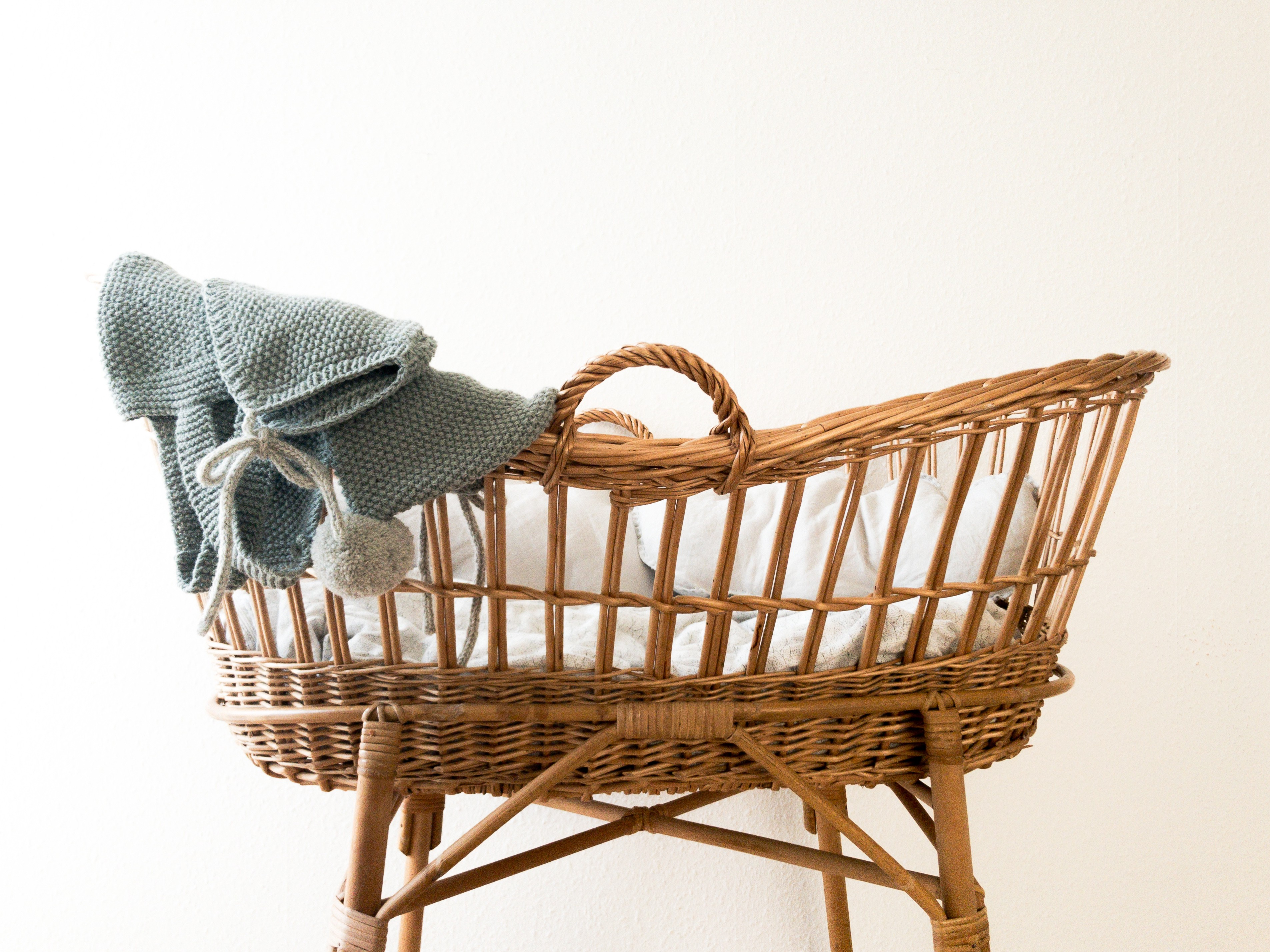 A woven bassinet/moses basket with white bedding and a grey knit baby jacket draped on one end.