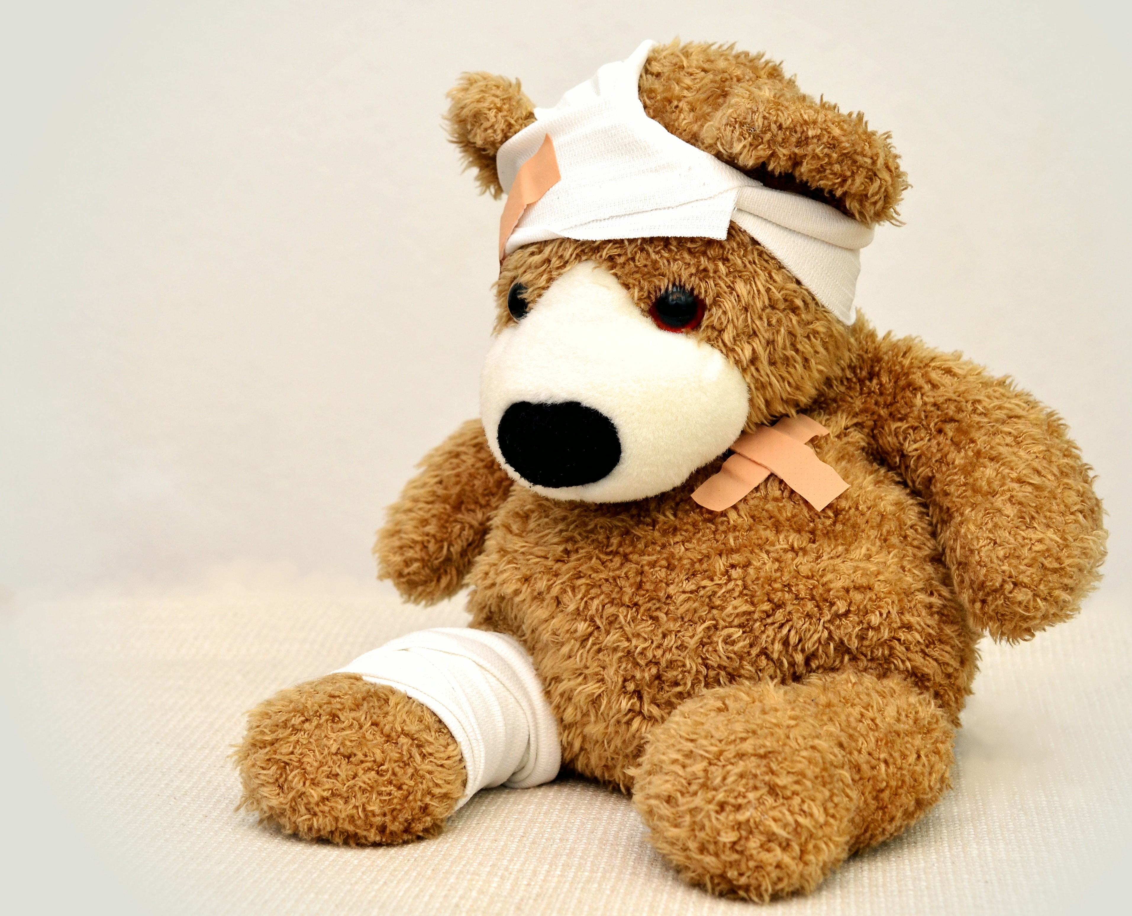 Photograph of a light brown teddy bear with bandaids on its heart, bandages and bandaids on its head, and a bandage on its right leg.
