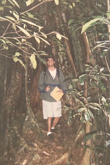 A photo of Ramesh Laungani standing in the Australian rainforest. He is surrounded by a variety of trees and plants.