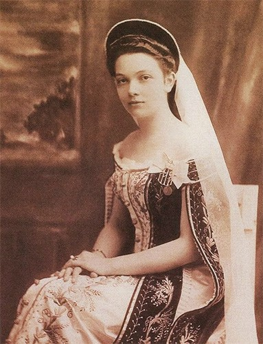 A lady-in-waiting in Russian court dress with a fabric kokoshnik, veil, and off-the-shoulder dress with long split sleeves.