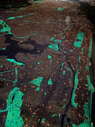 Close up of the Panorama exhibit in the dark at the Queens Museum, with areas of the city glowing in the dark.