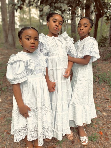 Three young girls in ruffly white dress stand before a woodland.