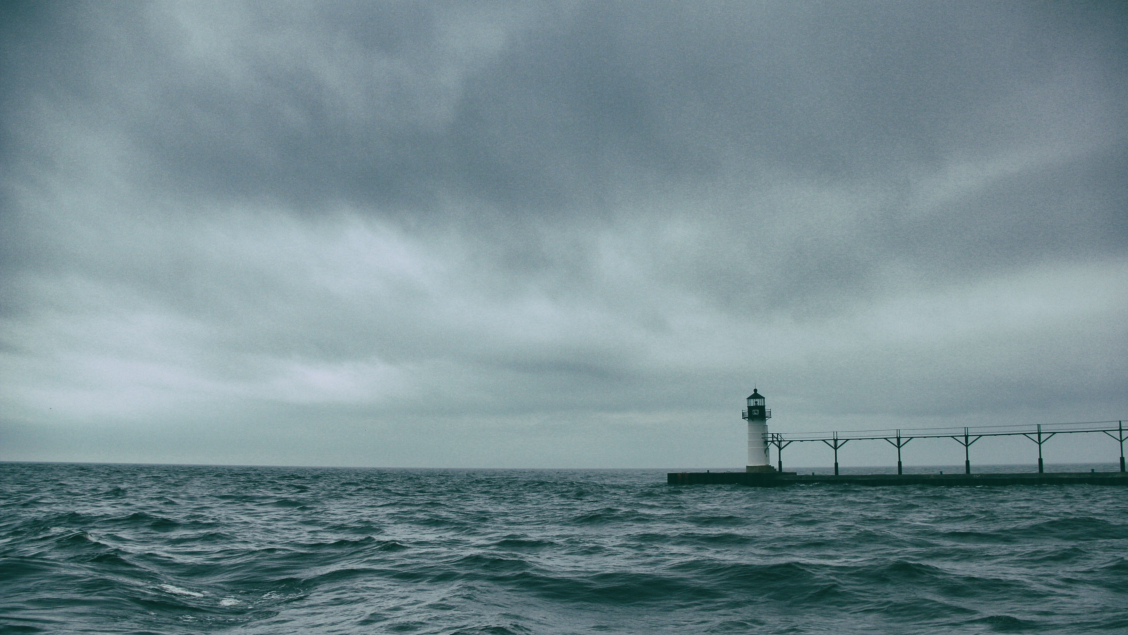 A lighthouse surrounded by water, with gray skies in the background