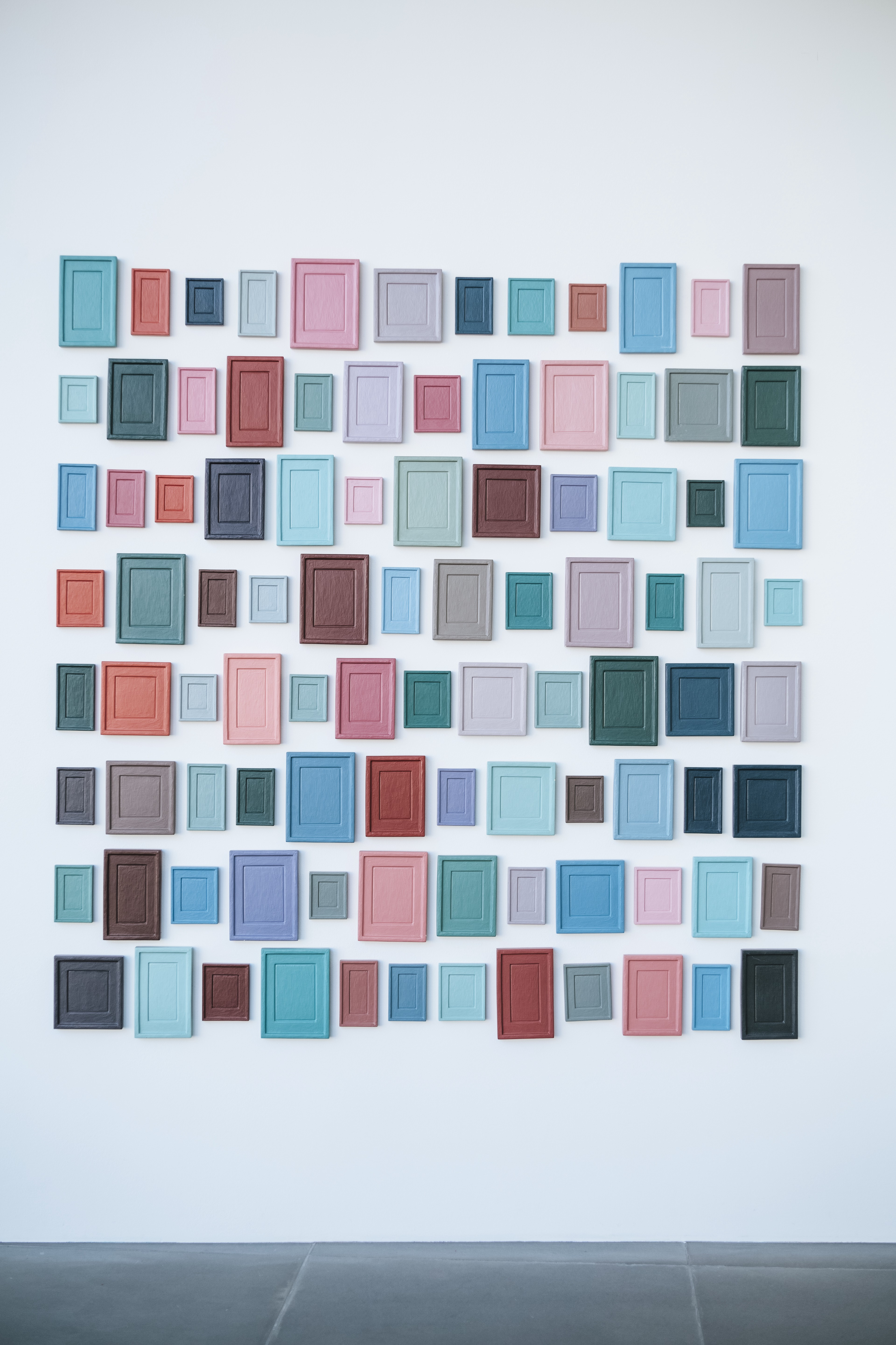 a wall of blank picture frames painted in different colors and organized in rows and columns