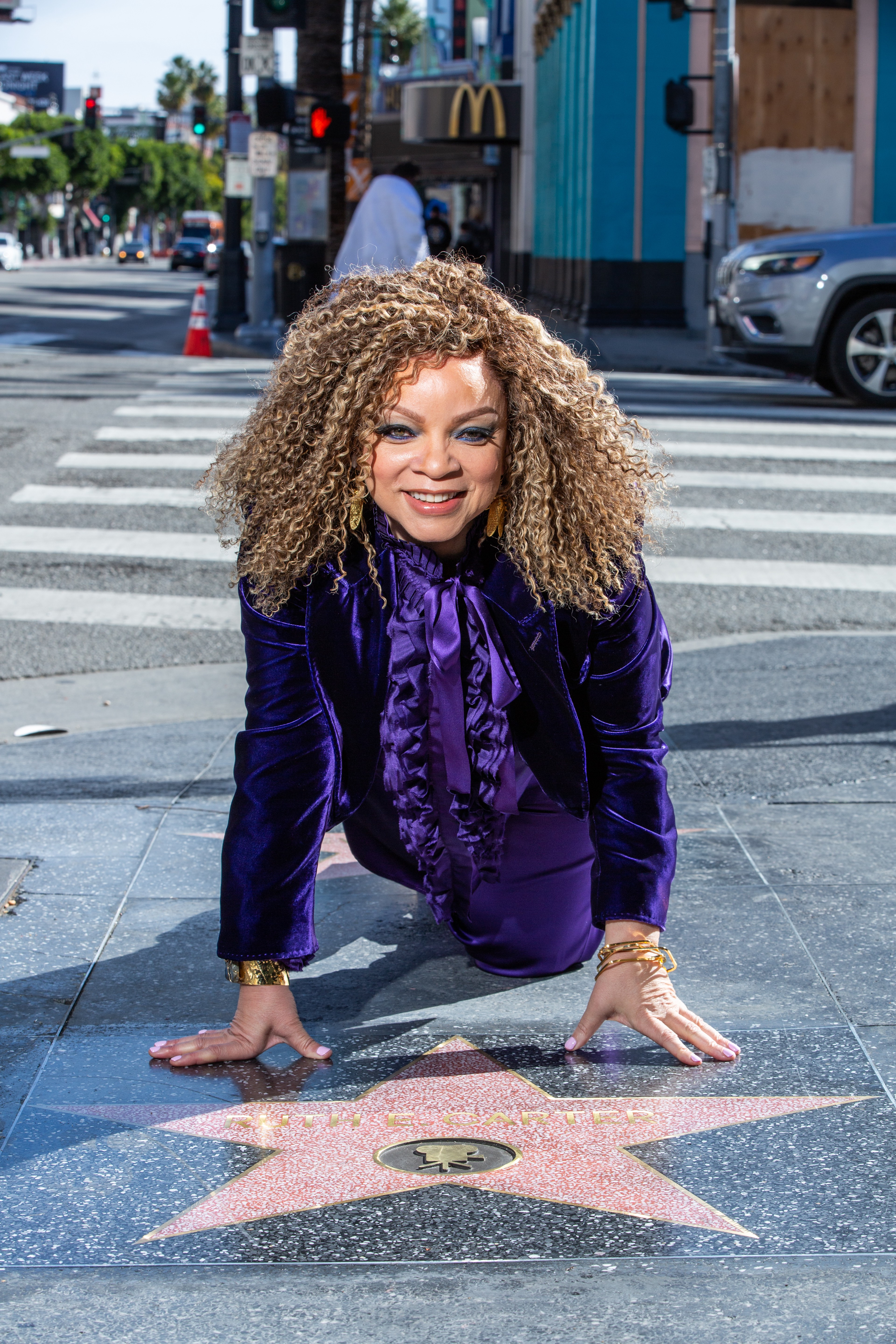 Ruth Carter posing and kneeling next to her Hollywood Walk of Fame star.