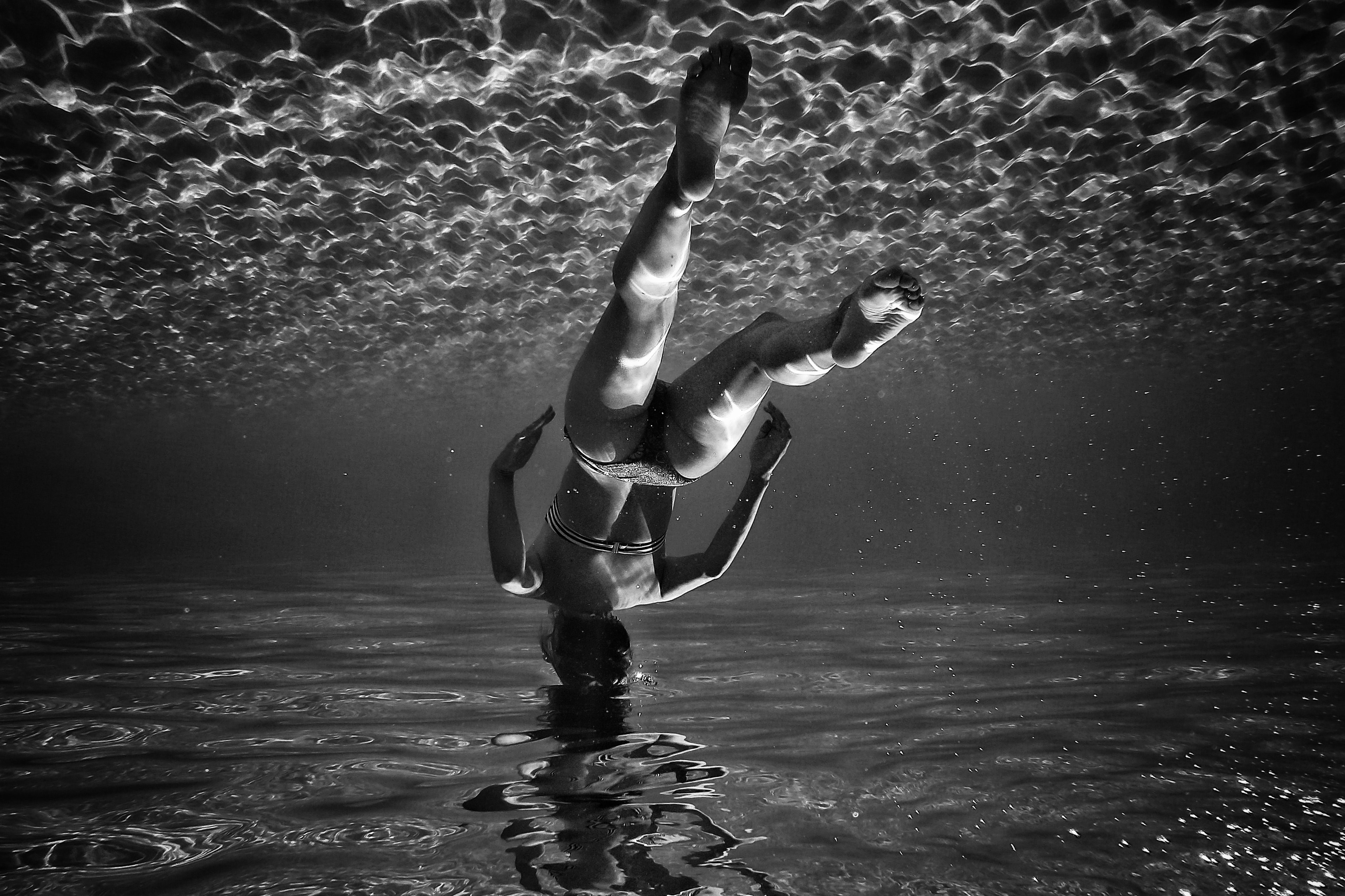 Black and white reflection of woman upside underwater.