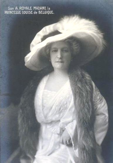 Louise as an older woman. She's wearing a white dress, fur stole, and a large white picture hat over her graying hair.