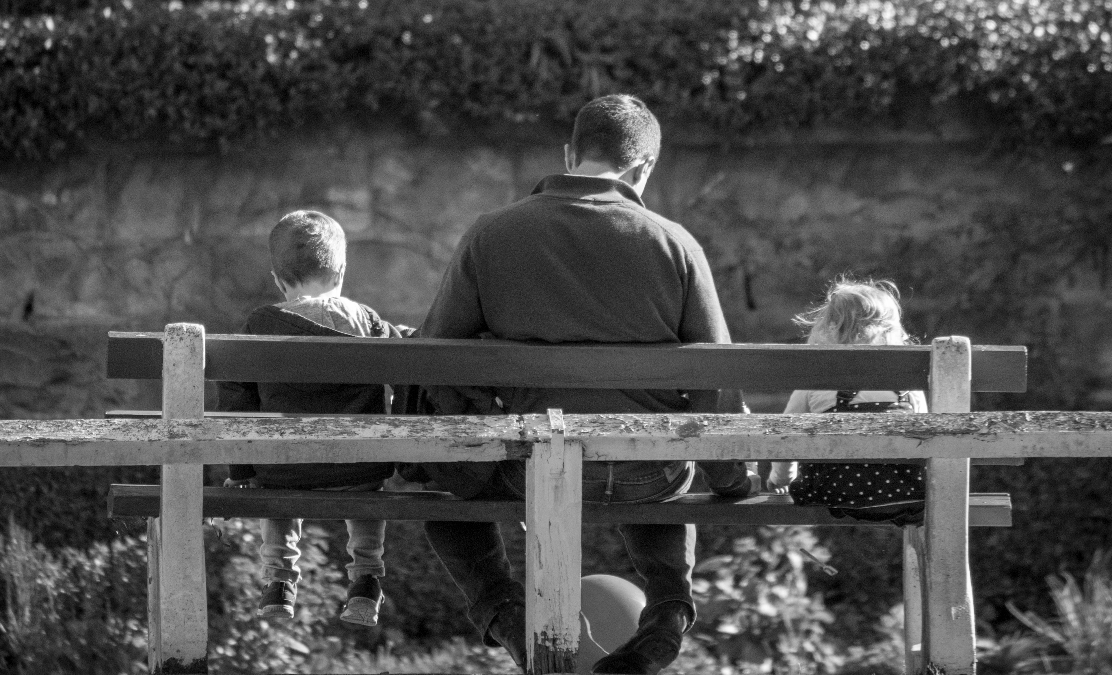 black and white photo of father with young son and daughter sitting on wooden bench