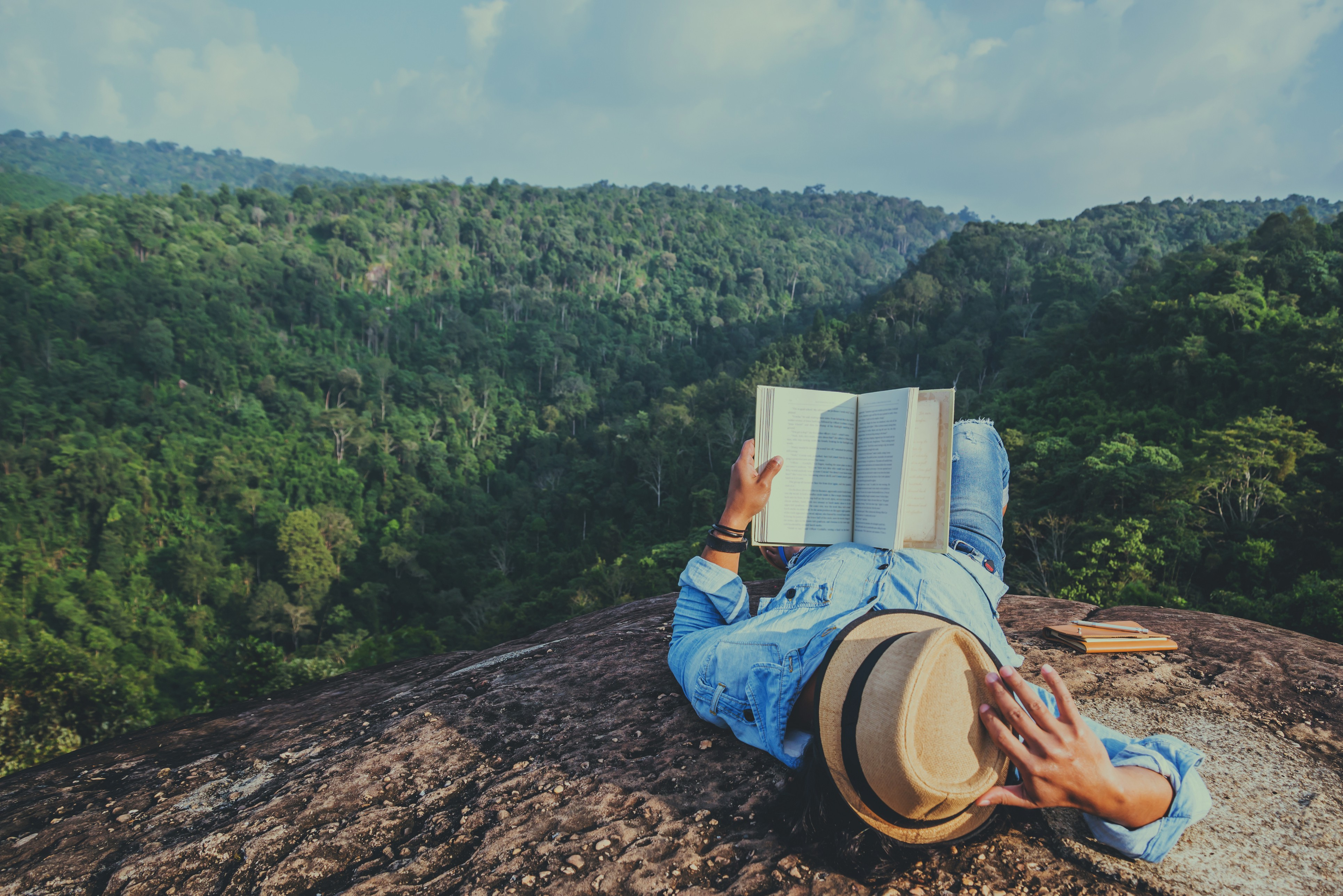 Woman reading a book in front of a scenic mountainous area