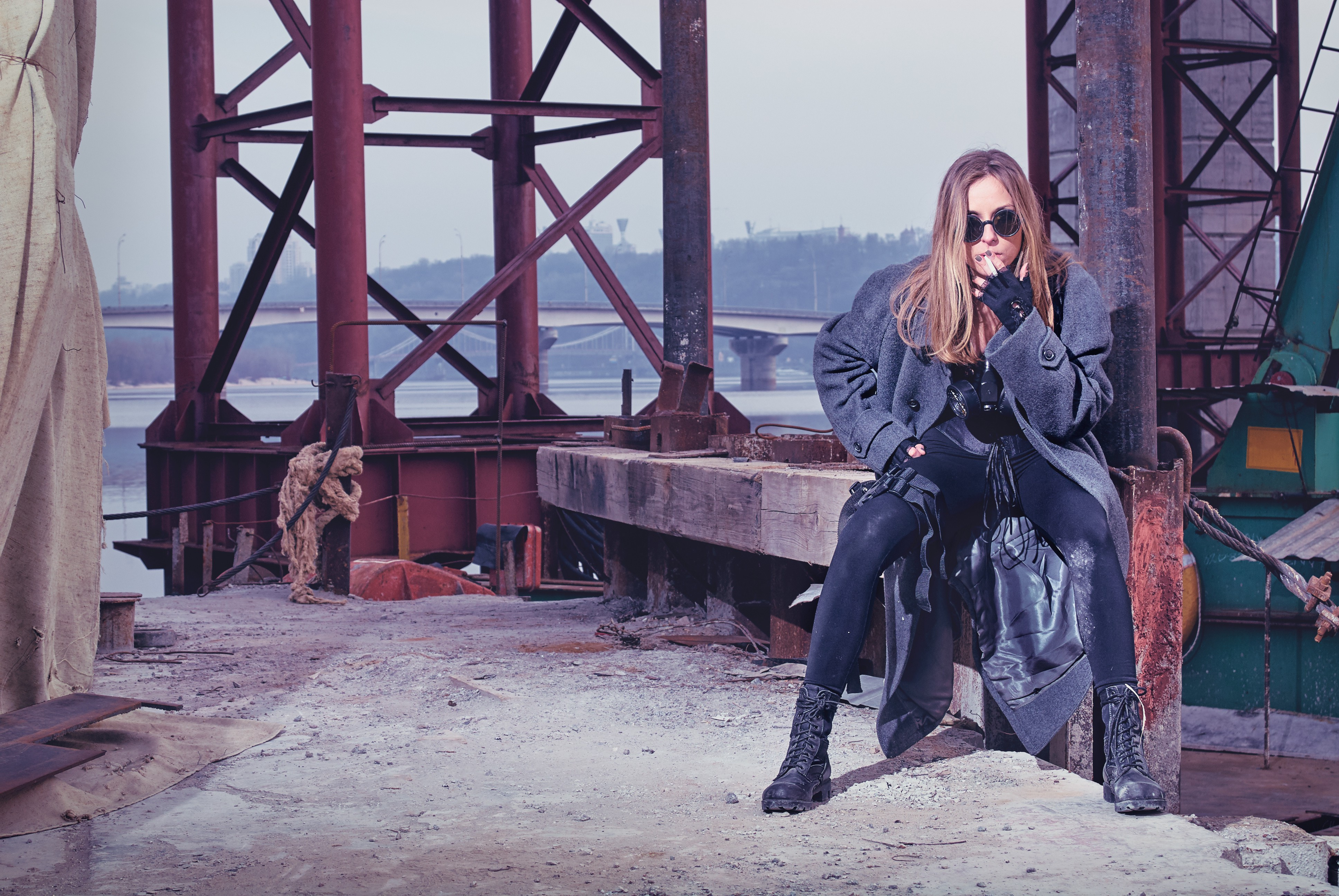 Woman in trench coat, dark clothing and sunglasses waiting for someone under a bridge