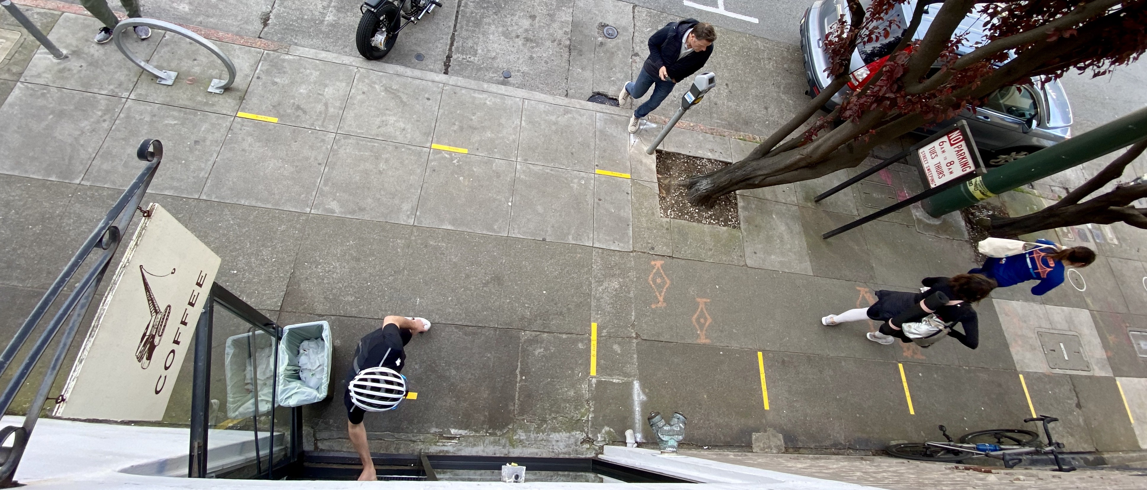 an overhead photo of the sidewalk with yellow tape lines indicating where people should stand