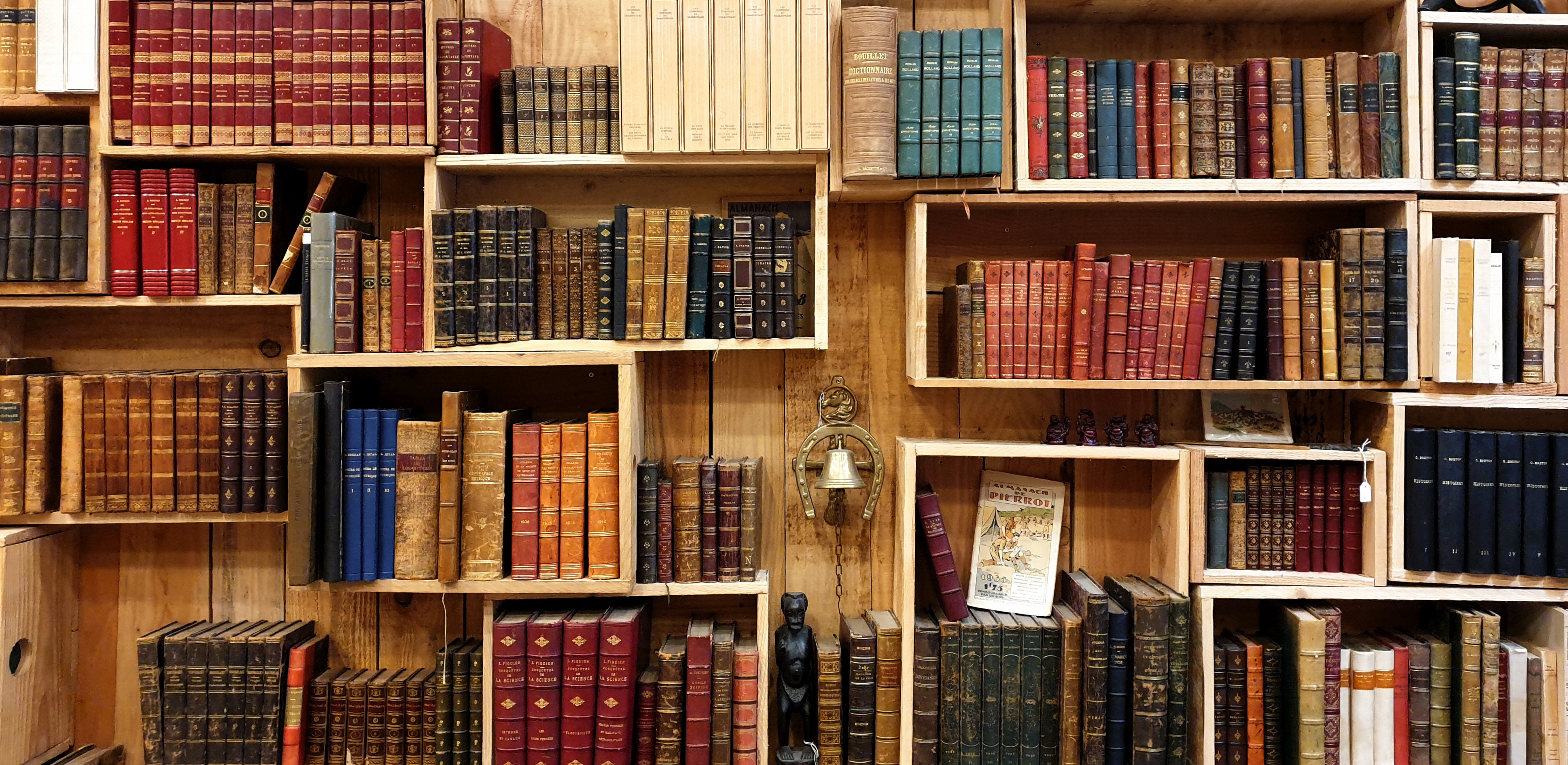 Shelves that look like boxes hold vintage books upon a wooden wall.