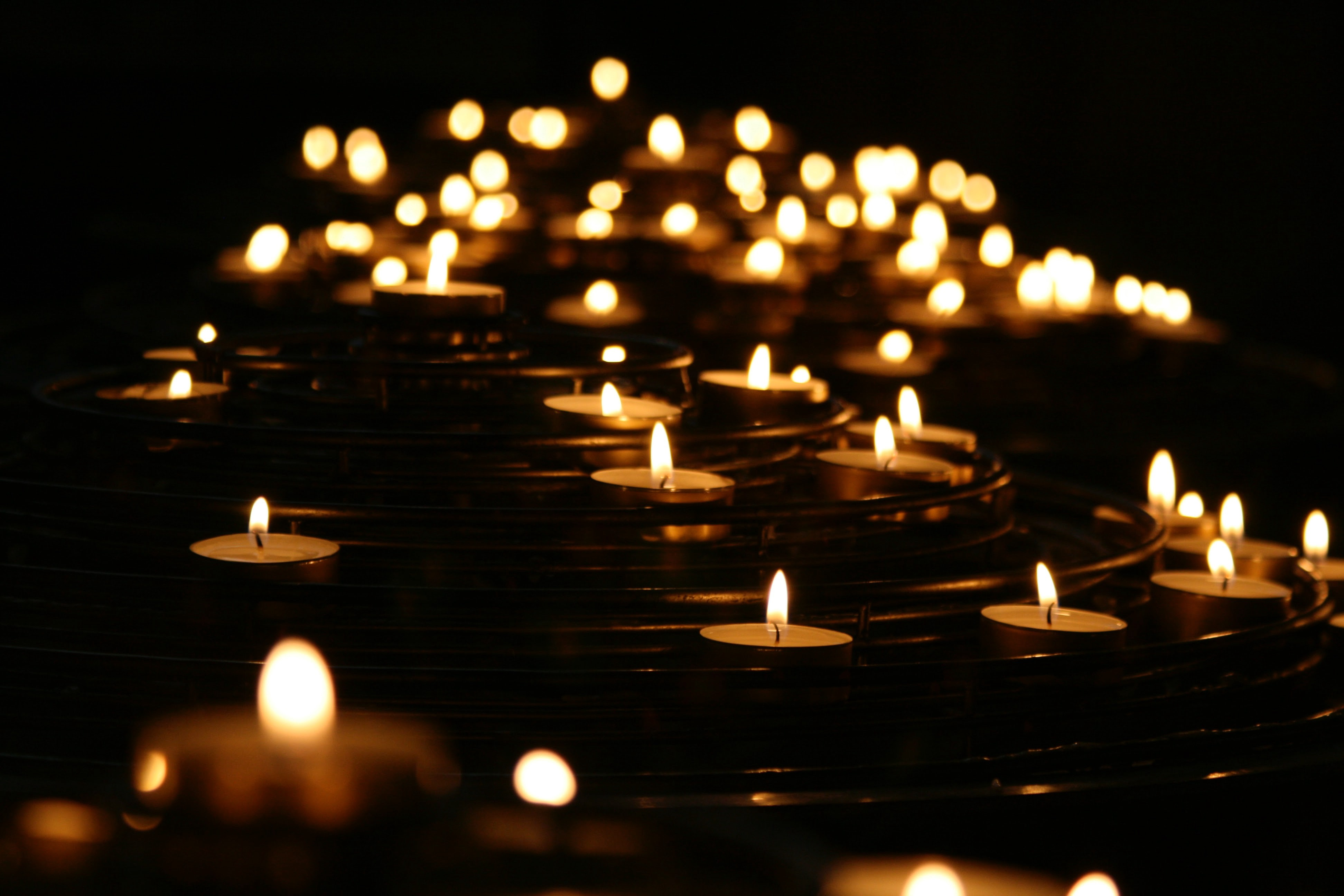 Votive candles floating on a dark sea