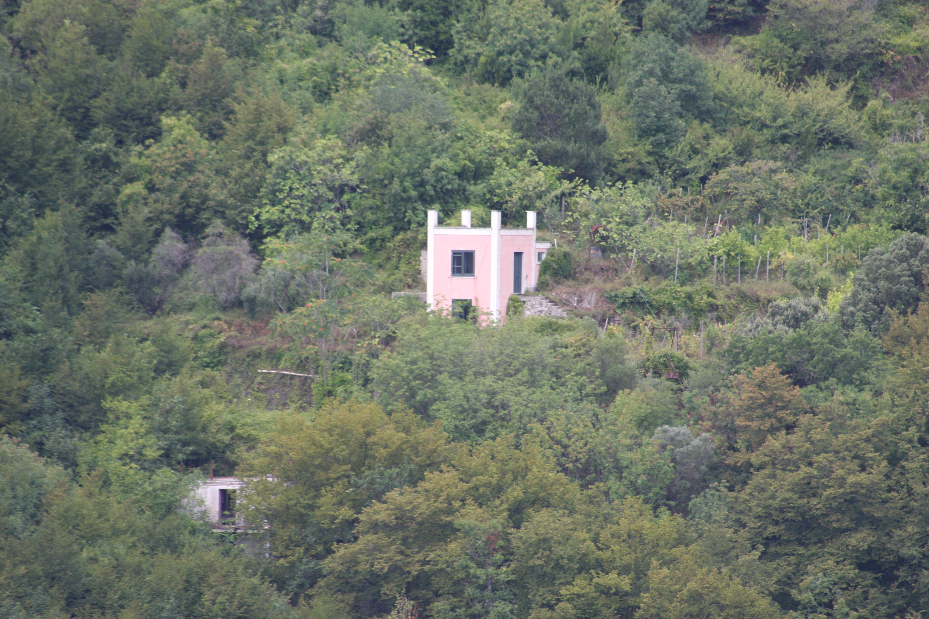 A small building nested on a hill surrounded by trees