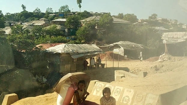 Some smiling children sitting on the side of the dirt roads at kutupalong refugee camp