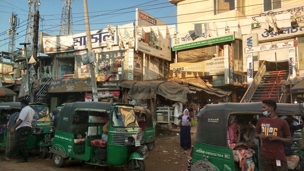 Clustered dirt paved street filled with people and green tuk tuks in Cox's Bazar