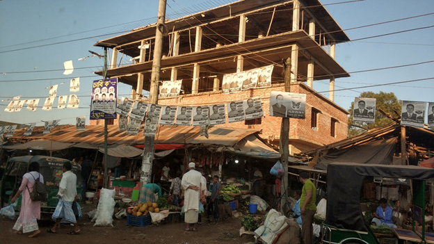 A crowded market in Cox's Bazar with political campaign posters