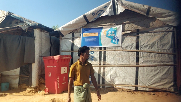 """A man walks past an IOM tent with the words """"Information is Aid"""" at kutupalong refugee camp"""
