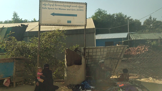 A family of four sells clothing items on the side of the road at kutupalong camp