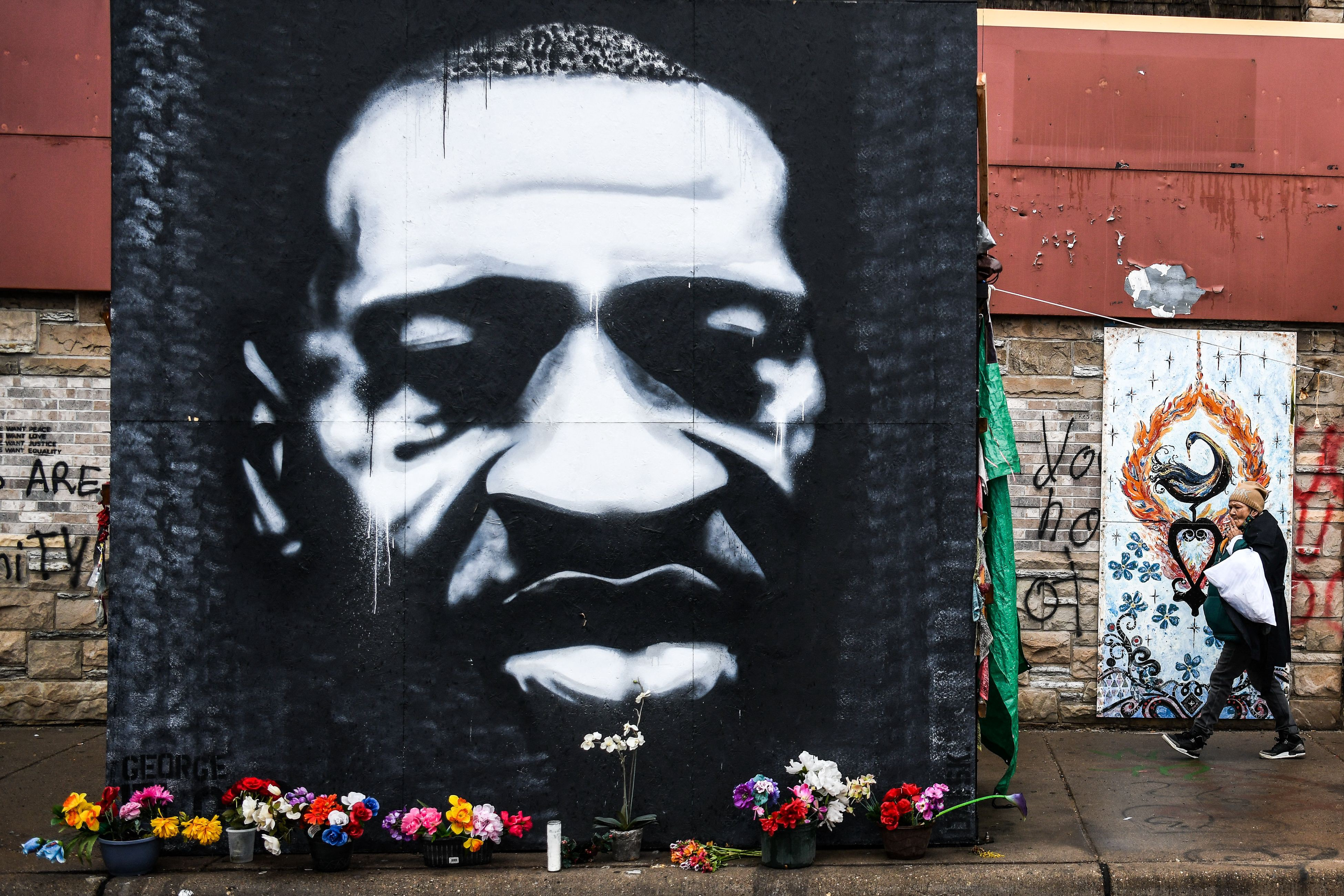 Black and white mural of George Floyd with flowers resting in front.