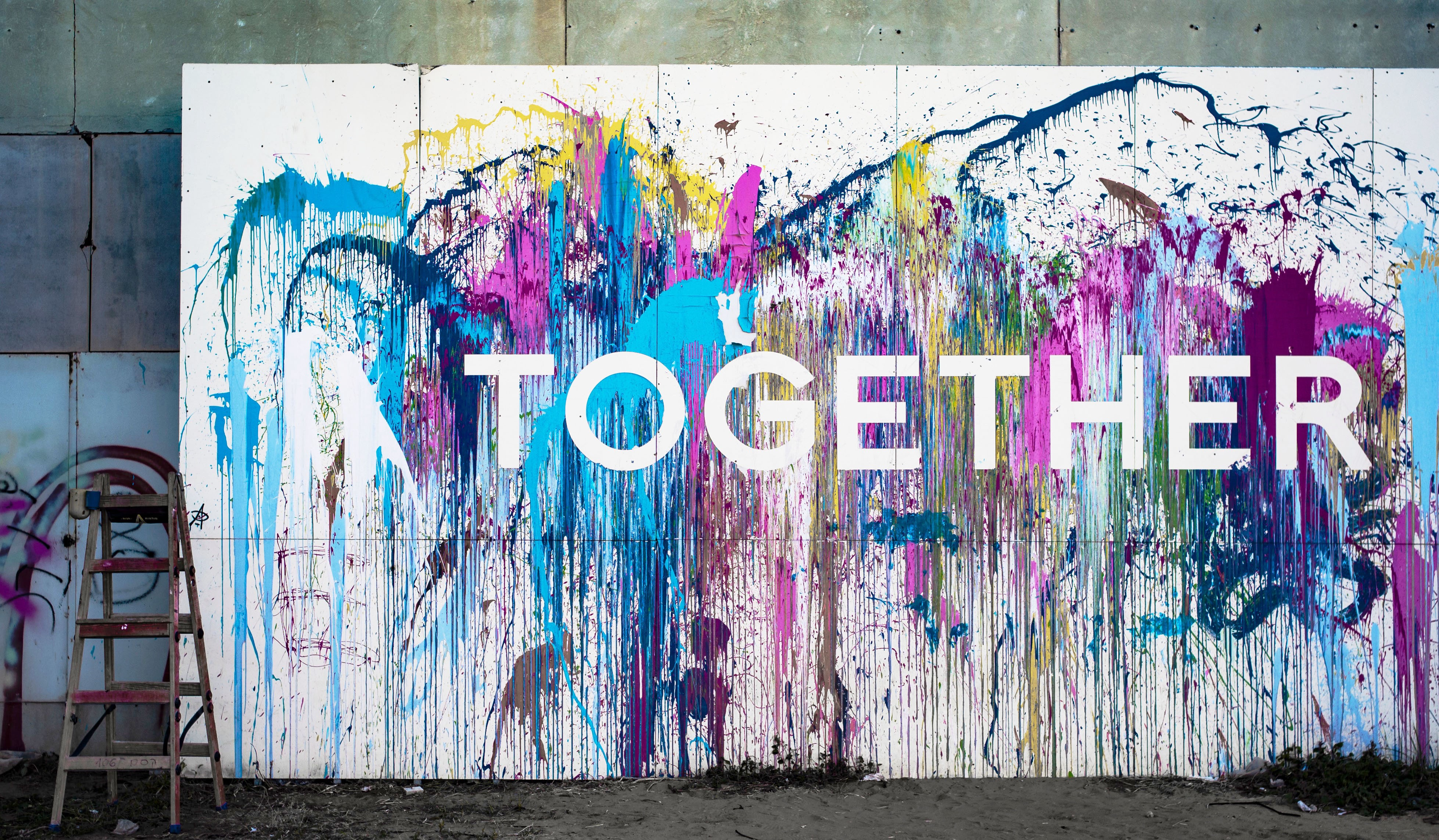 """A painting of the word """"together."""" Whole Communities–Whole Health is a grand challenge at The University of Texas at Austin."""