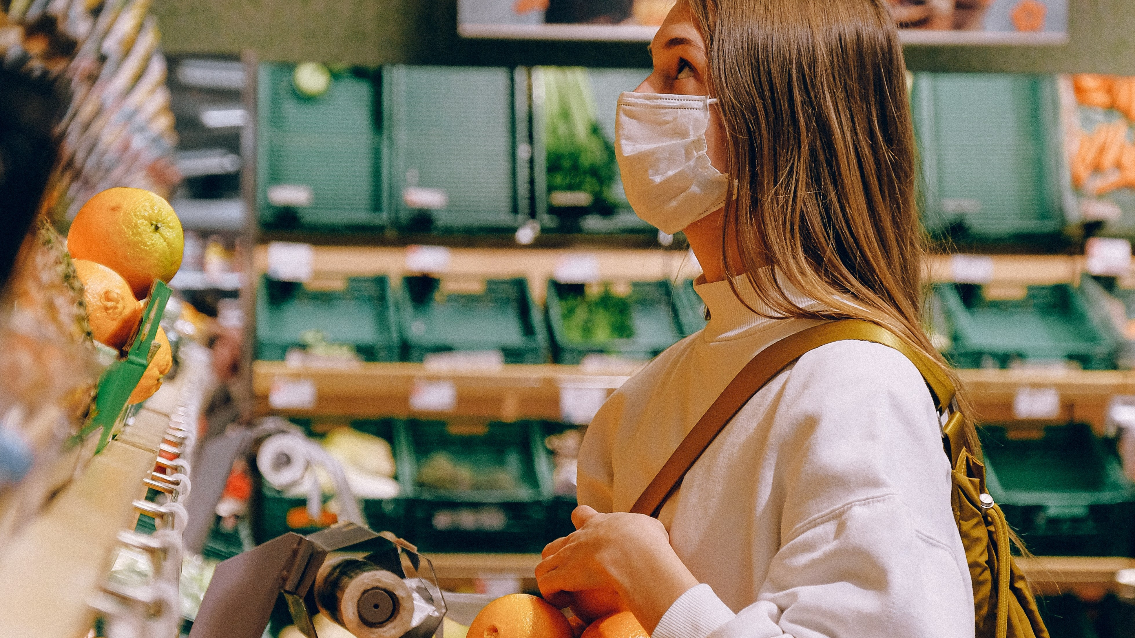 A woman wearing a mask shopping in a supermarket