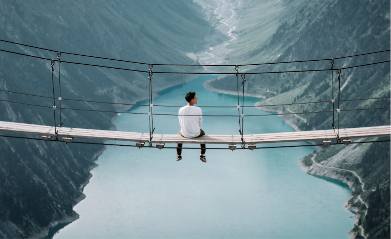 A person sits in the middle of a swing bridge, high above a mountainous lake