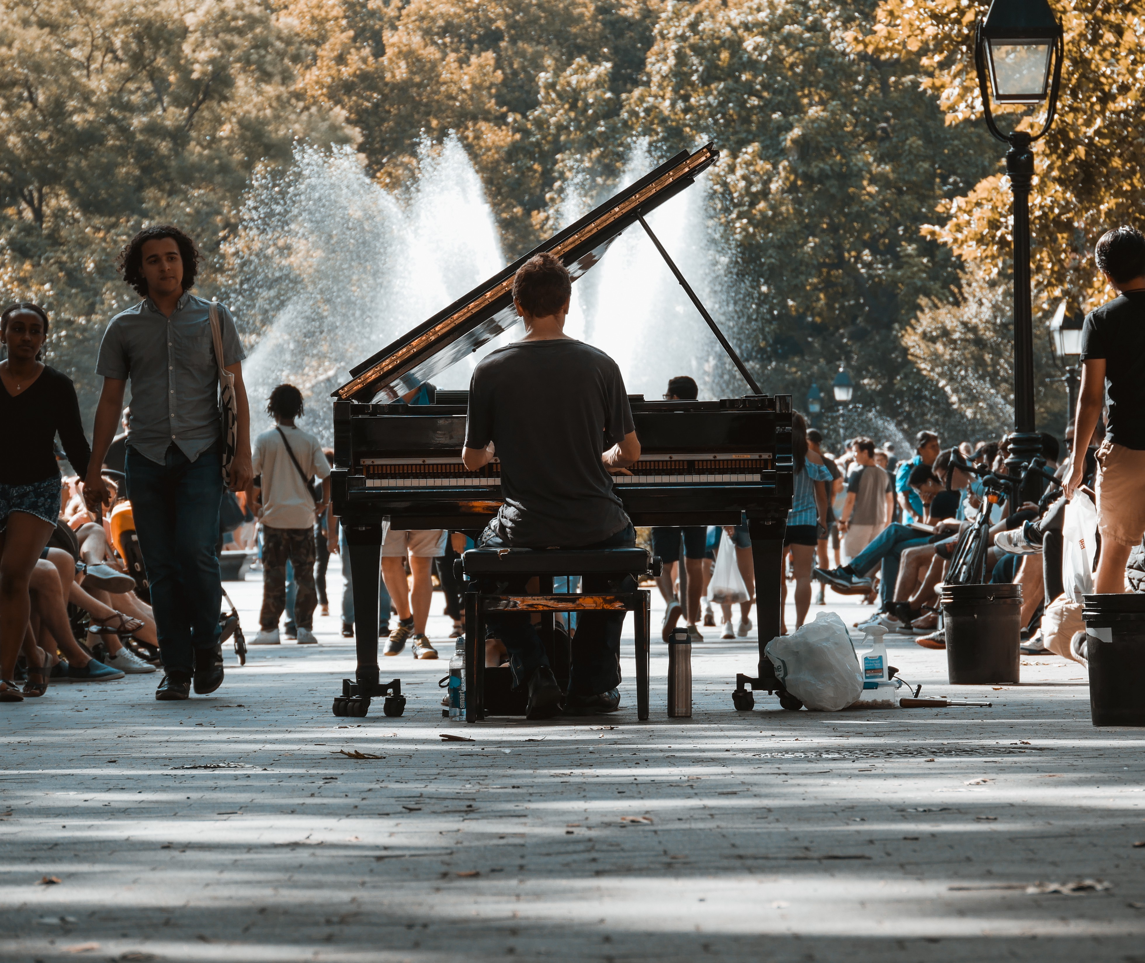 Rear view of a man playing piano in an outdoor park.