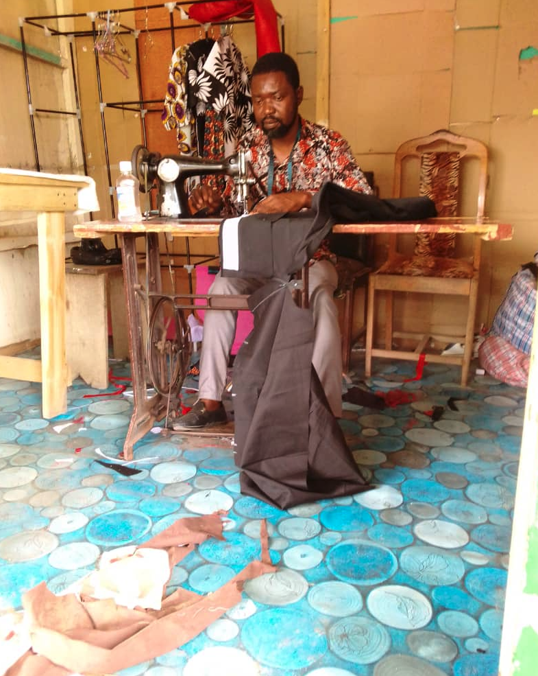 John Botwe of Assin Foso, Ghana, who has recently pivoted to sewing nose masks. Seen sewing male garments.