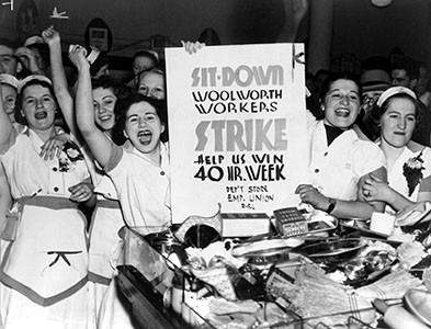 Women store clerks raise their fists and raise a sit-down strike sign demanding a 40-hour work week for Woolworth workers.