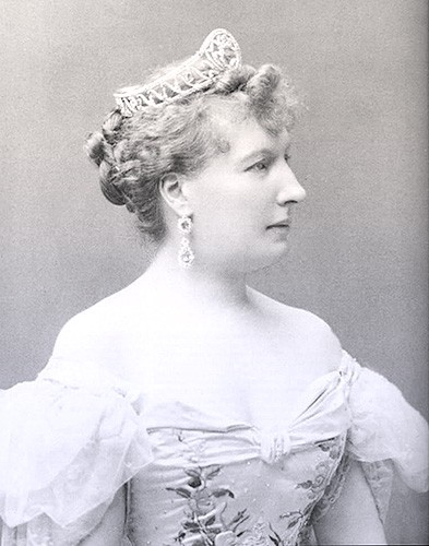 Louise in profile, wearing an off-the-shoulder ball gown and tiara.