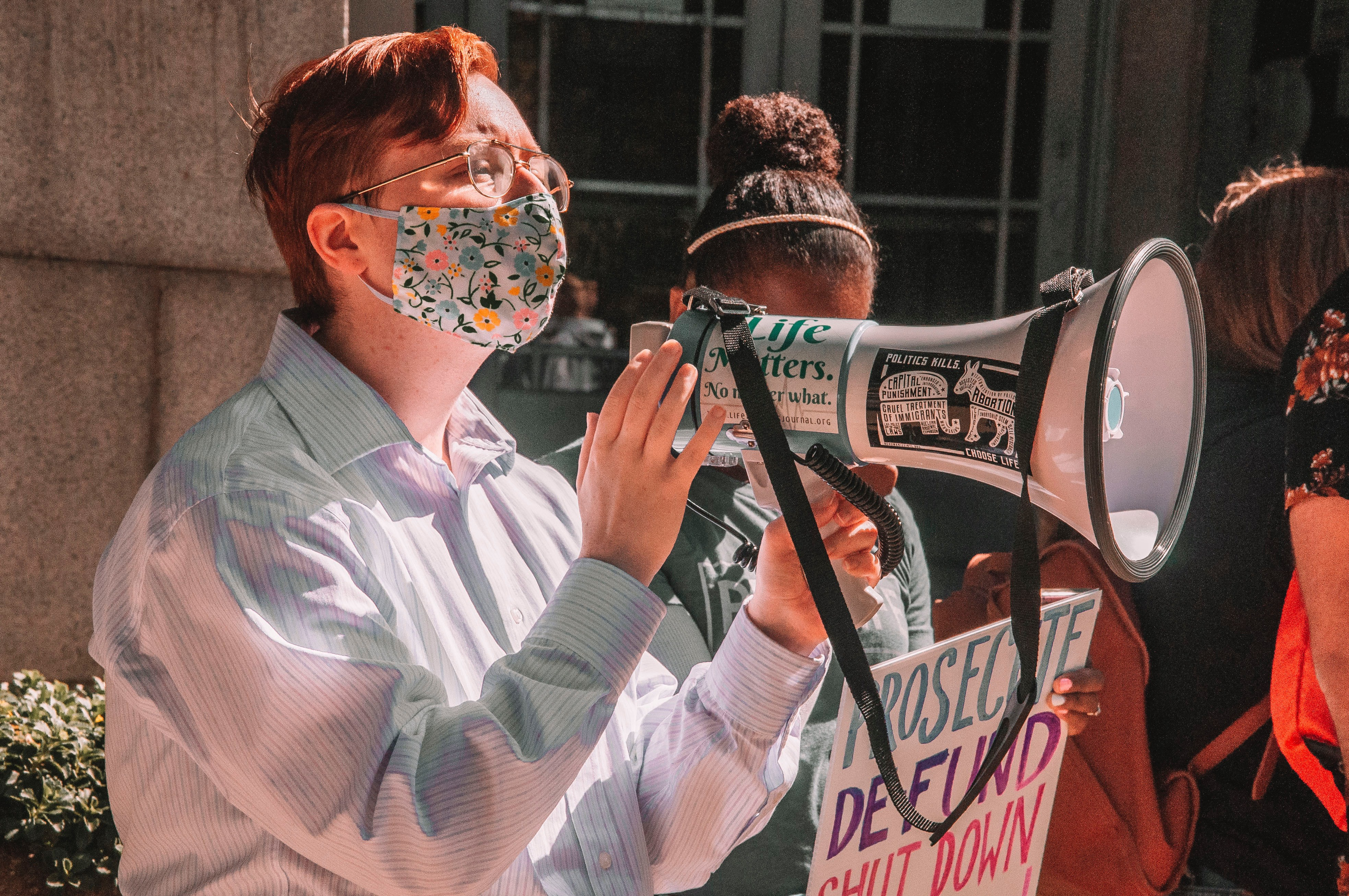 activist holding a large white megaphone and a face mask