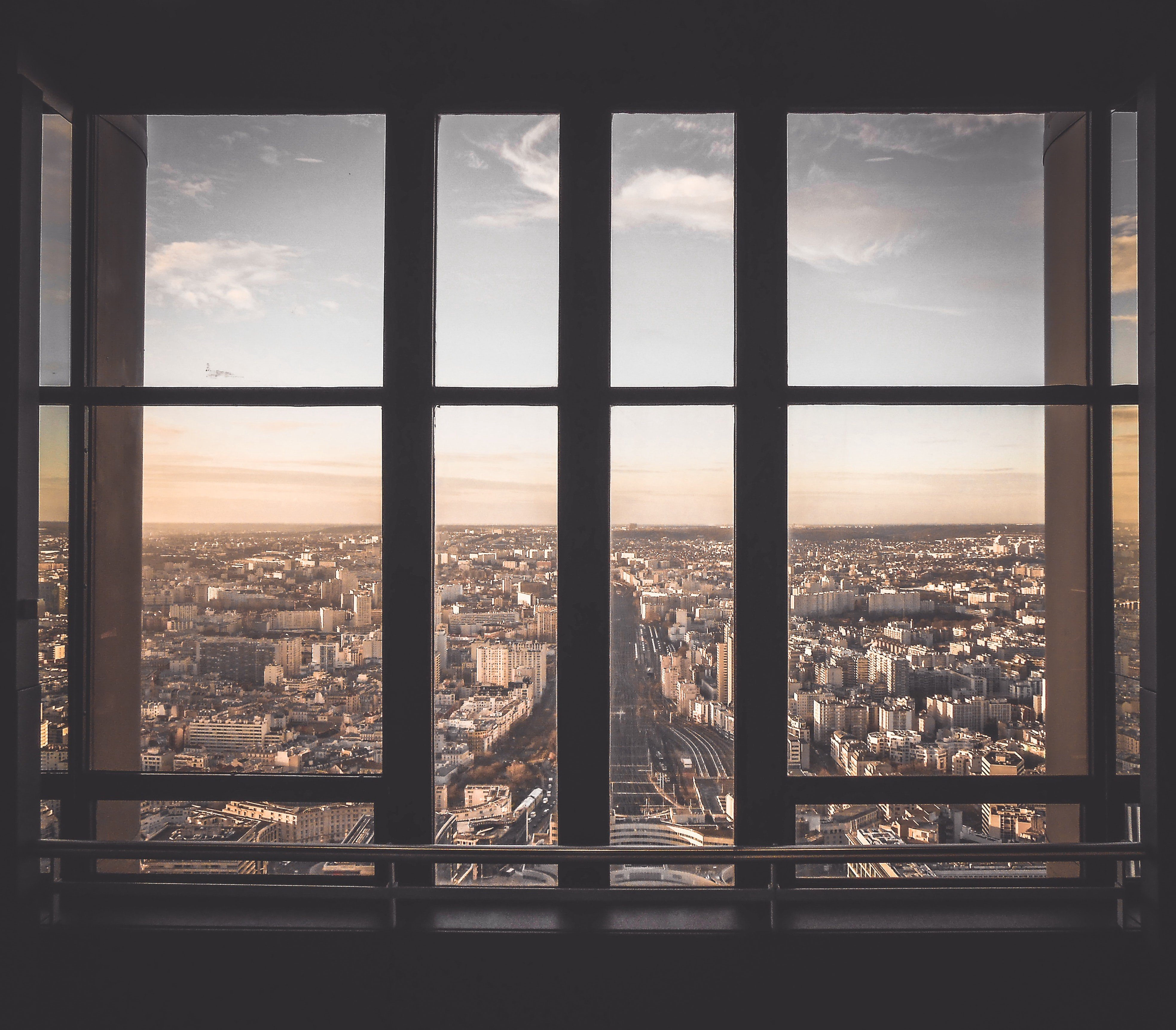 A window looking out over a city, slid partway open