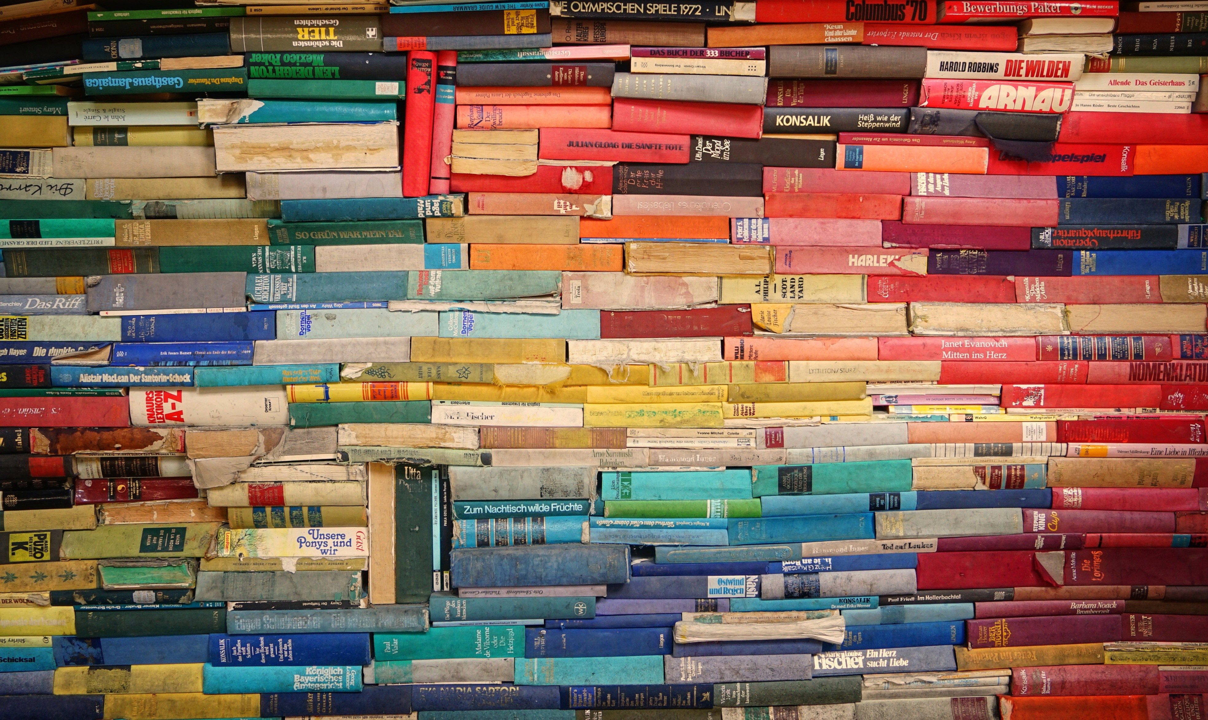 A pile of old, fading books arranged in a quasi-rainbow pattern