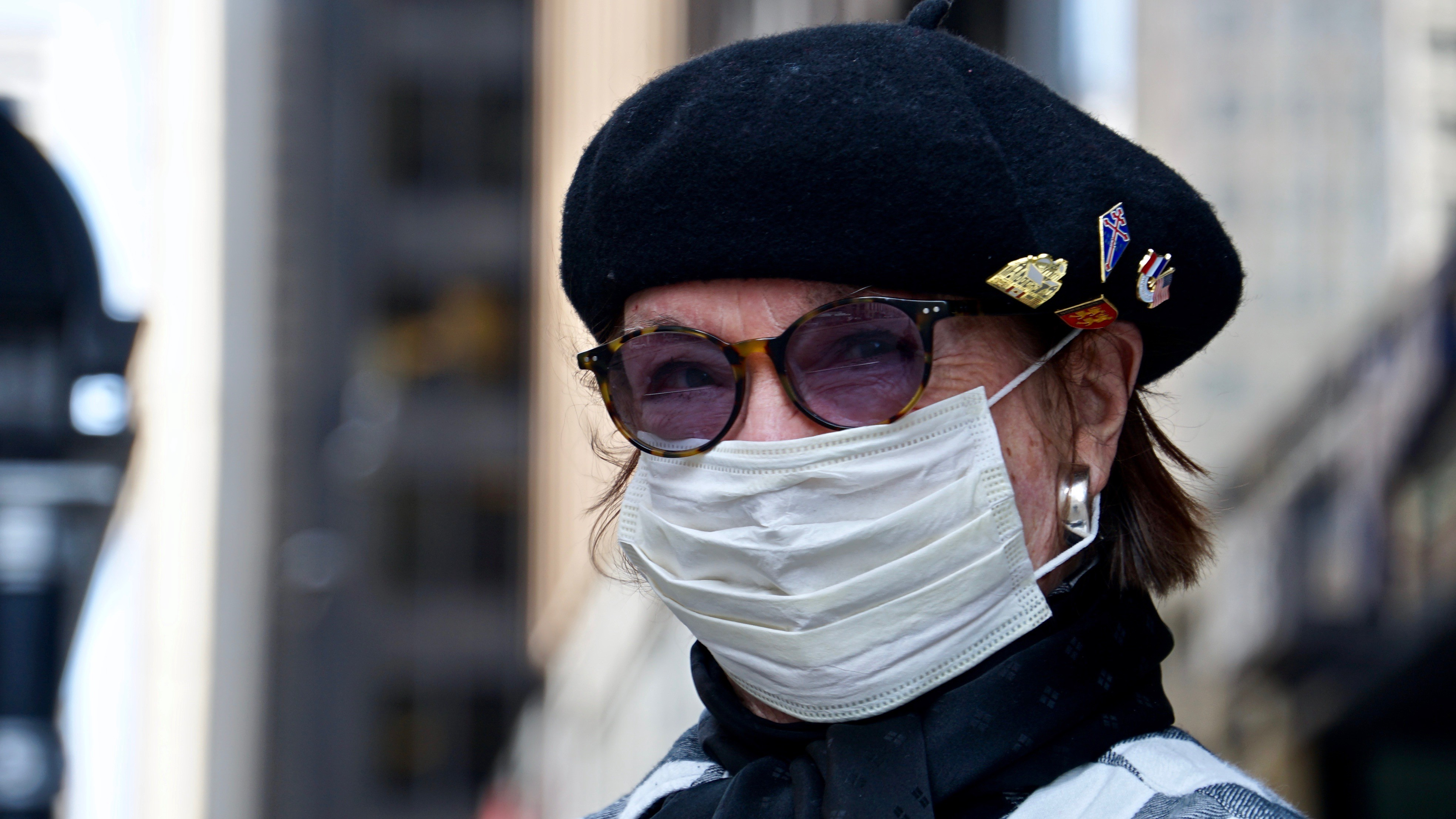 A medical mask and sunglasses can't cover up her expression.