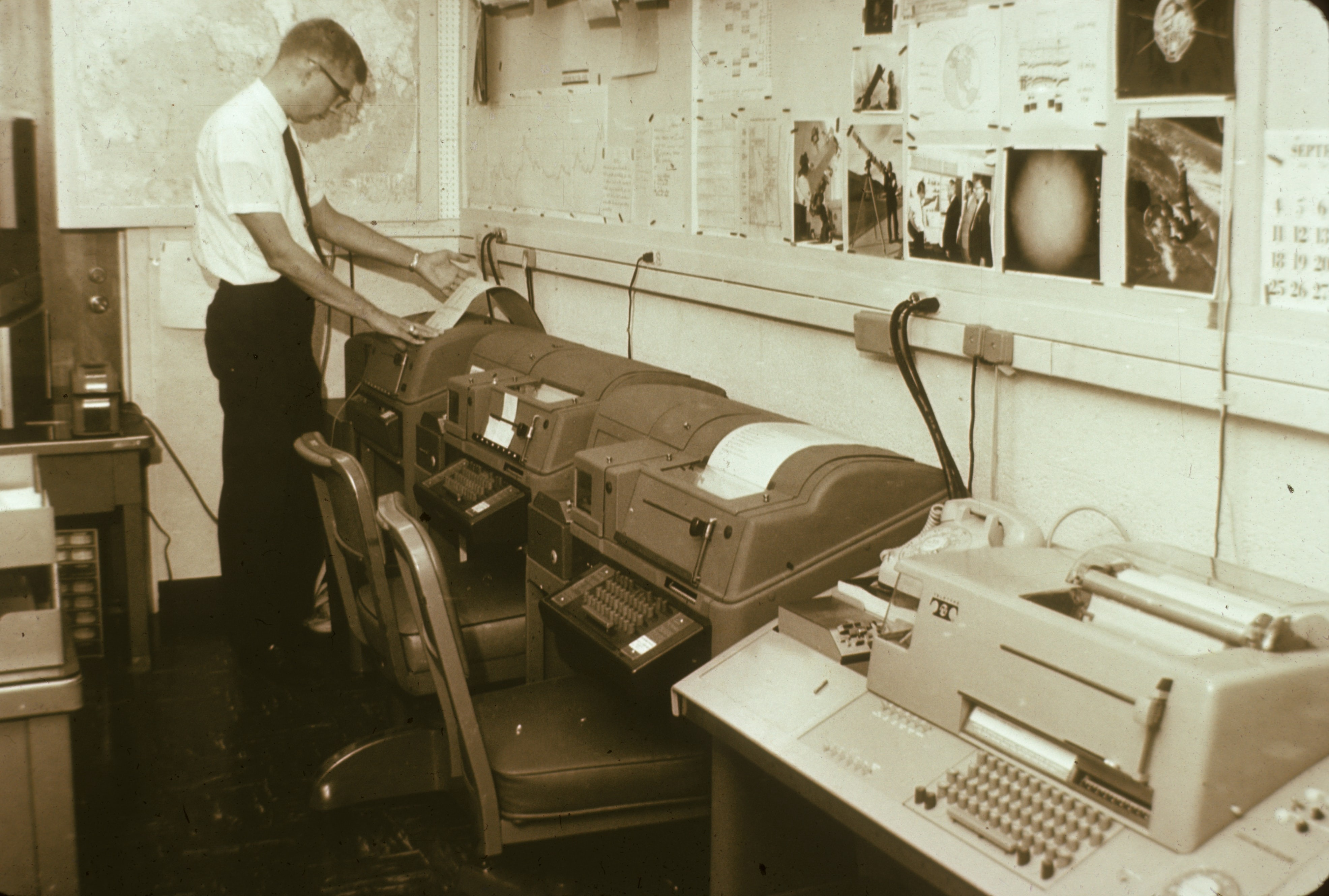 Sepia-tinted picture of man working on old-fashioned computers