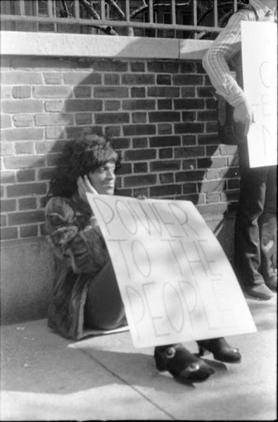 """A black and white photo of Marsha P Johnson sitting against a brick wall at a protest. She holds a sign that reads, """"POWER TO THE PEOPLE""""."""